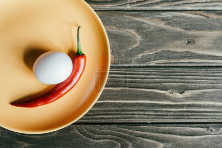 Chili pepper and egg in plate on wooden table