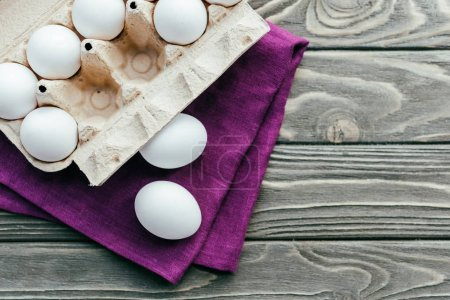 Carton box with white eggs on purple napkin