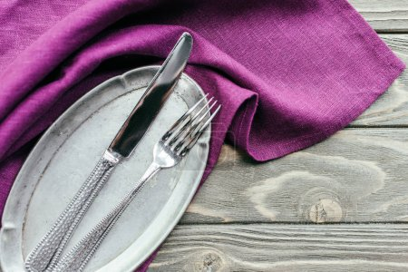 Silver tray with cutlery on purple napkin