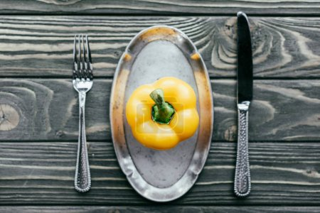 Yellow bell pepper served on plate with knife and fork on wooden table