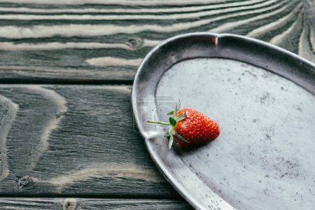Ripe red strawberry on silver tray on wooden table