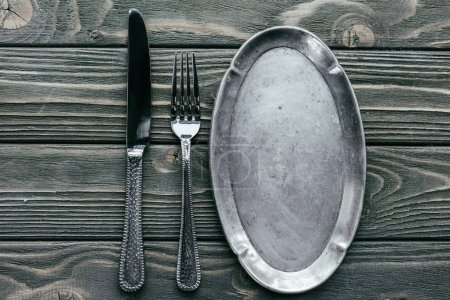 Photo for Knife and fork with silver tray on wooden table - Royalty Free Image
