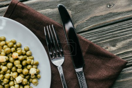 Fork and knife by plate with peas on textile napkin