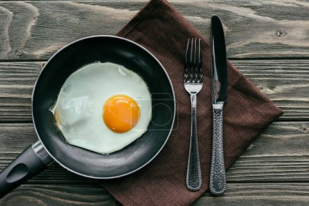 Frying pan with egg and cutlery set on textile napkin