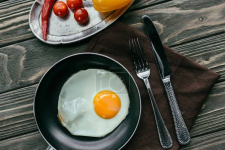 Raw vegetables and frying pan with egg on textile napkin