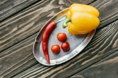 Peppers and cherry tomatoes in silver tray on wooden table