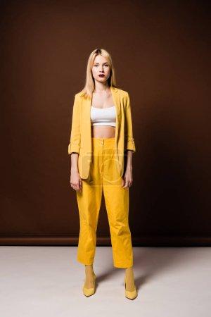 Photo pour Pleine longueur vue de belle fille blonde en tenue jaune à la mode en regardant la caméra sur brun - image libre de droit