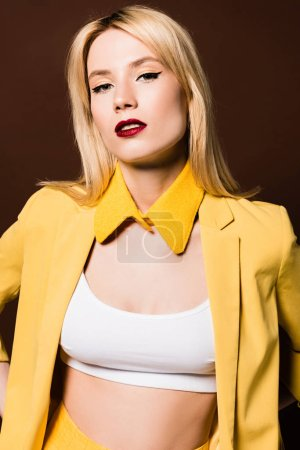 portrait of beautiful blonde girl in fashionable yellow clothes looking at camera isolated on brown