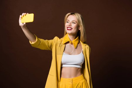 beautiful smiling stylish blonde girl taking selfie with yellow smartphone isolated on brown