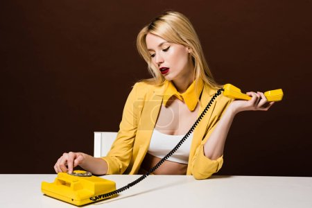 beautiful stylish blonde woman in yellow clothes using rotary phone while sitting on brown