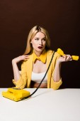 attractive blonde girl holding yellow handset and looking away on brown