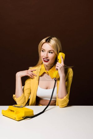 beautiful smiling blonde girl in stylish yellow clothes talking by rotary phone and looking away on brown