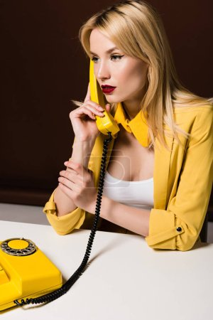 stylish blonde girl in yellow clothes talking by rotary phone and looking away on brown