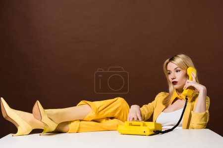 beautiful pensive stylish girl talking by yellow telephone and looking away on brown