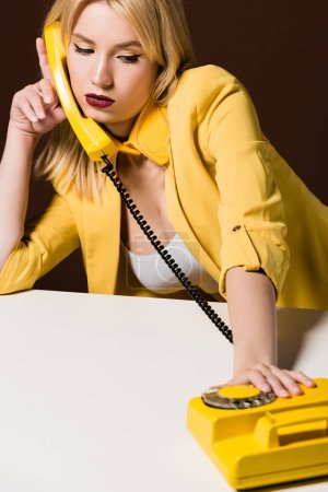beautiful pensive young woman talking by yellow rotary phone on brown