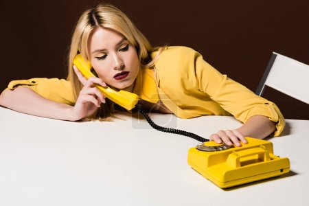 Photo for Beautiful young woman talking by yellow rotary phone on brown - Royalty Free Image