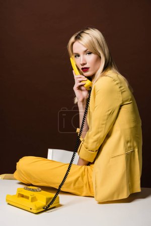 attractive stylish blonde woman in yellow clothes talking by rotary phone and looking at camera on brown