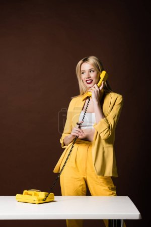 Photo for Beautiful stylish blonde woman talking by yellow vintage phone and looking away on brown - Royalty Free Image