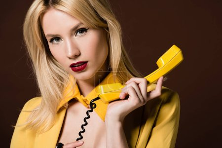 attractive blonde woman holding yellow handset and looking at camera isolated on brown