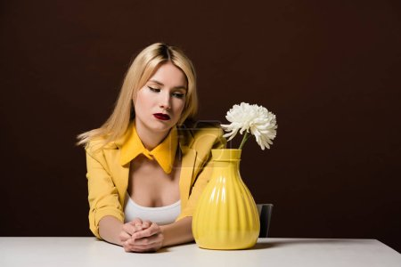 beautiful stylish blonde woman looking at white flower in yellow vase on brown