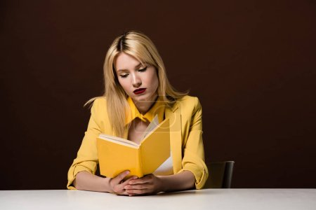 beautiful fashionable blonde woman reading yellow book on brown