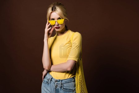 stylish blonde girl with string bag wearing yellow sunglasses and looking at camera isolated on brown