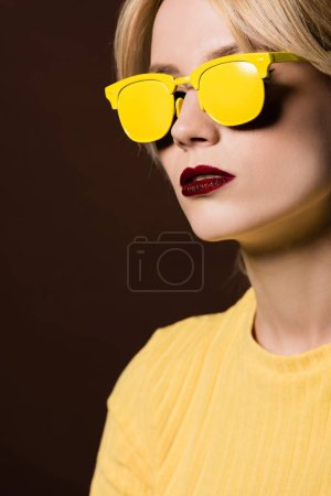 portrait of beautiful blonde girl wearing yellow sunglasses isolated on brown