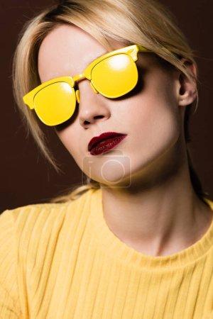 Foto de Primer plano retrato de hermosa chica rubia con gafas de sol amarillo aislados en marrón - Imagen libre de derechos