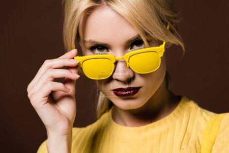 close-up portrait of beautiful young blonde woman in yellow sunglasses looking at camera isolated on brown