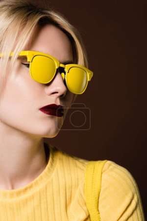 close-up portrait of beautiful young blonde woman wearing yellow sunglasses isolated on brown