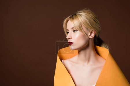beautiful blonde woman wrapped in orange paper looking away isolated on brown