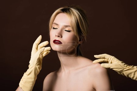 human hands in yellow gloves touching seductive naked blonde girl on brown