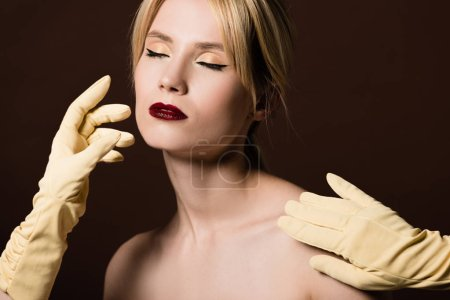 naked blonde girl with closed eyes and human hands in yellow gloves on brown