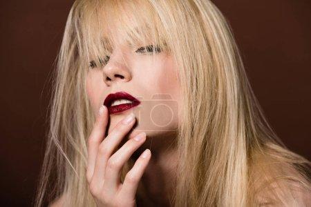 seductive beautiful blonde woman posing on brown