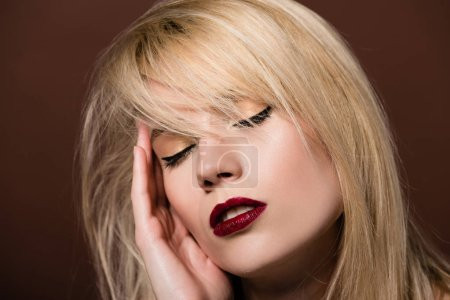 portrait of sensual young blonde woman with closed eyes posing on brown