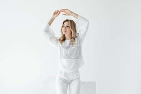 beautiful pensive blond woman in white clothing posing isolated on white