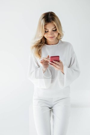 smiling blond woman in white clothing using smartphone isolated on grey