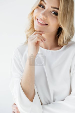 portrait of beautiful smiling woman in white clothing looking at camera on white background