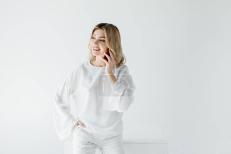 portrait of smiling blond woman in white clothing talking on smartphone isolated on grey