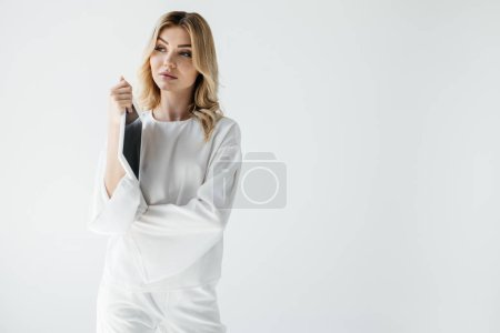 portrait of pensive woman in white clothing with tablet isolated on grey