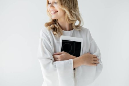 portrait of young smiling woman in white clothing with tablet on grey backdrop