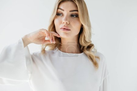 portrait of pensive blond woman in white clothing posing on white backdrop