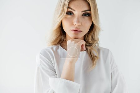portrait of beautiful blond woman in white clothing posing on white backdrop