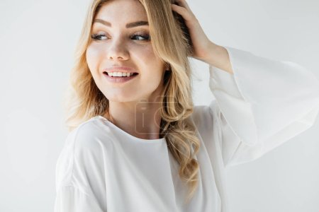 portrait of beautiful smiling woman in white clothing looking away on white backdrop