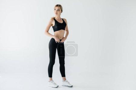 beautiful sportswoman in black sportswear standing isolated on grey