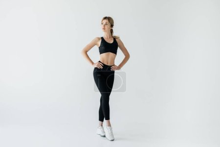 beautiful sportswoman akimbo in black sportswear standing isolated on grey