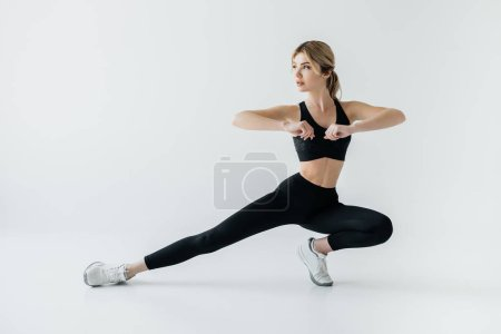 Photo for Young athletic sportswoman exercising isolated on grey - Royalty Free Image