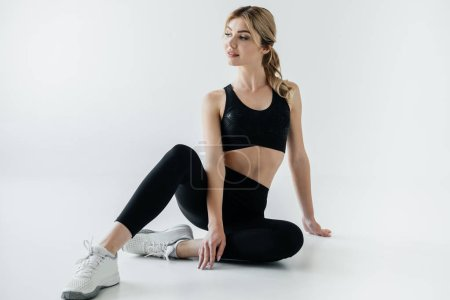 attractive sportswoman in black sportswear sitting on floor isolated on grey