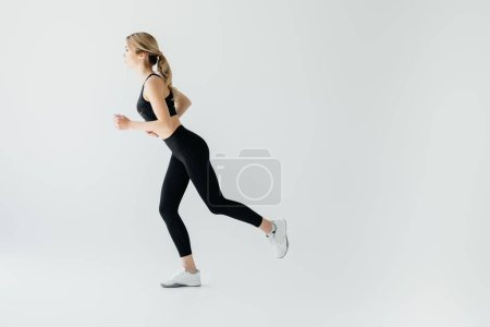 Photo for Side view of young athletic sportswoman running isolated on grey - Royalty Free Image