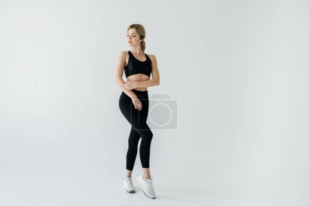 Photo for Young blond sportswoman in black sportswear posing isolated on grey - Royalty Free Image